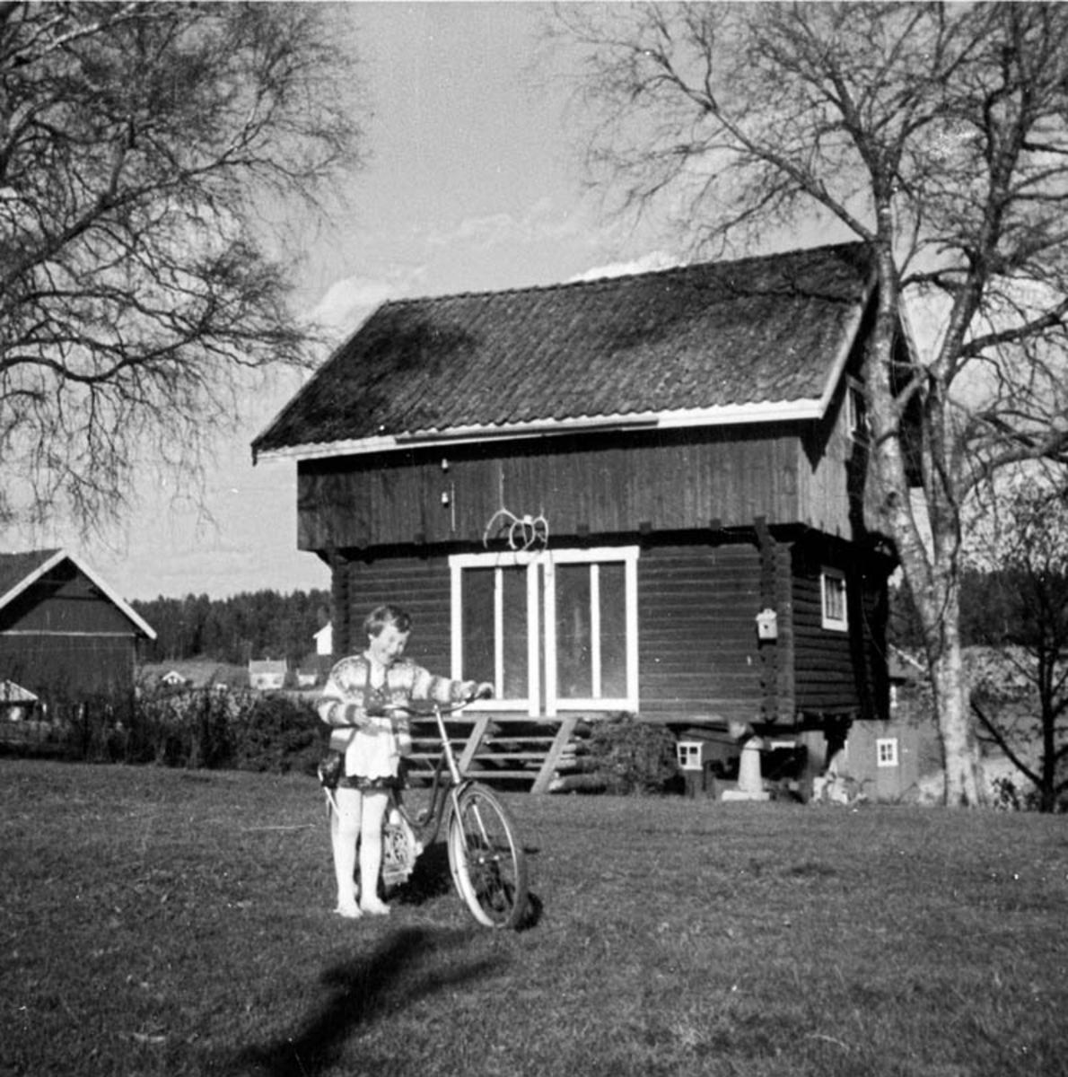 Jente med sykkel på tunet til Søgar'n Kjustad. Bua bygget 1941.