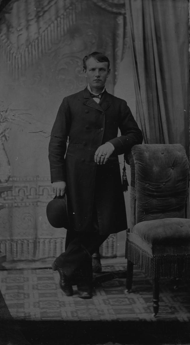 Karl Sørensen (Nord) Hammer står og lener seg til en stol.