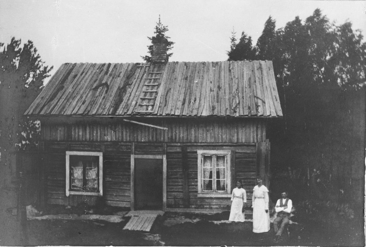 Bolighus med bordtak, 2 kvinner og en mann utenfor.
