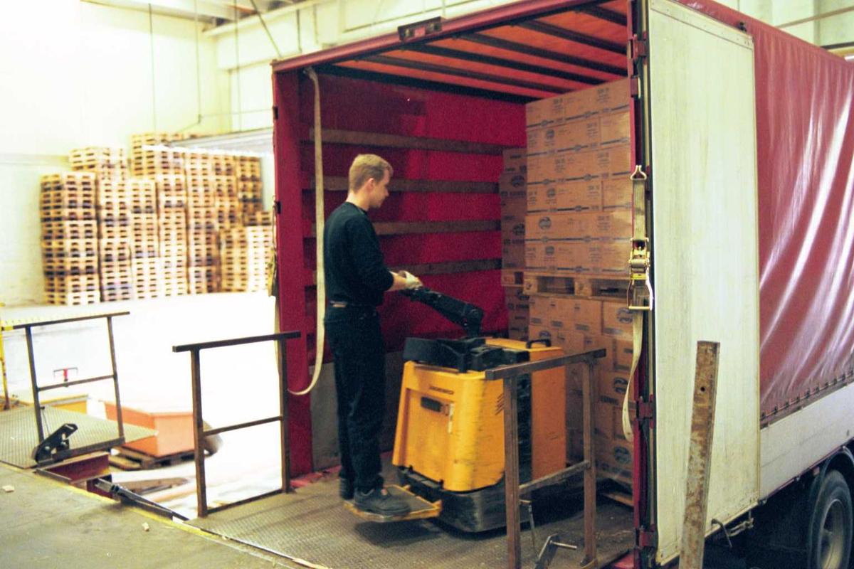 Gaffeltruck, lager, lastebil, emballasje, sjåfør. Pallene lastes på bil