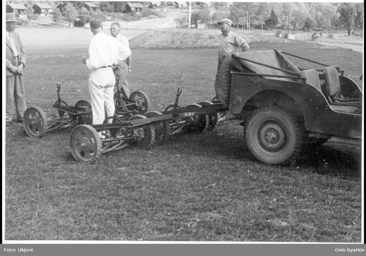 Inspeksjon av gressklipper-maskin, trukket av en jeep. Sanitetsforeningens hytter for tuberkuløse i bakgrunnen.