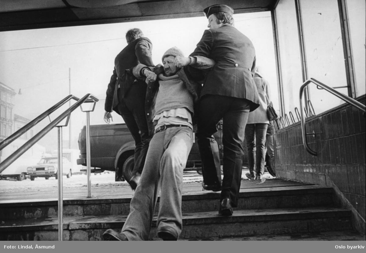 Alkoholiker fjernes fra stasjonsområdet av politiet. Uteligger. Fotografiet er fra prosjektet og boka ''Oslo-bilder. En fotografisk dokumentasjon av bo og leveforhold i 1981 - 82''. Kontakt Samfoto ved ev. bestilling av kopier.