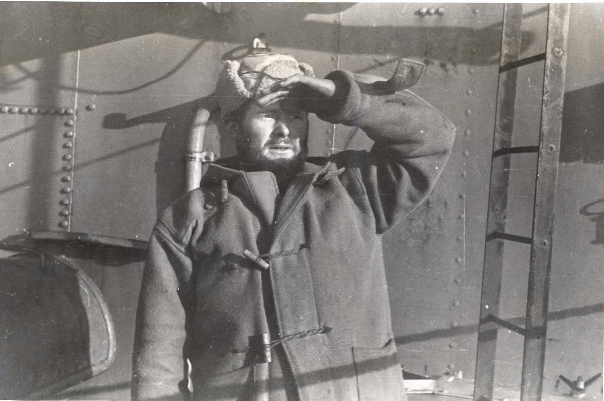 """Enkeltbilde. Jageren Stord i konvoy til Murmansk. En gammel veteran med navn """"Olsen med skjegget"""" speider utover havet."""
