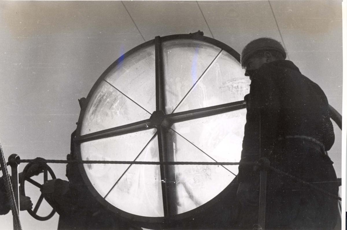 Enkeltbilde. Jageren Stord i konvoy til Murmansk. Søkelysene ombord blir polert og testet.
