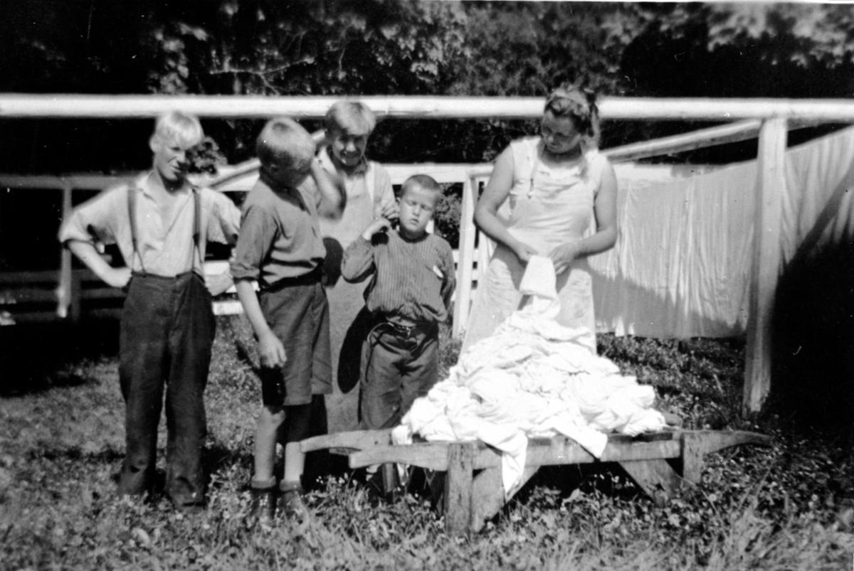 Klesvask på Toftes Gave, Nedre Sund, Helgøya. 1 jente og 4 gutter henger opp klær til tørk.