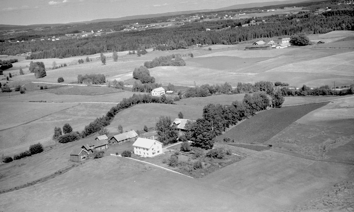 Flyfoto, Hestvold gård i Løten (ref. inventarnr. 0415-00584). I bakgrunnen sees Skillingstad.