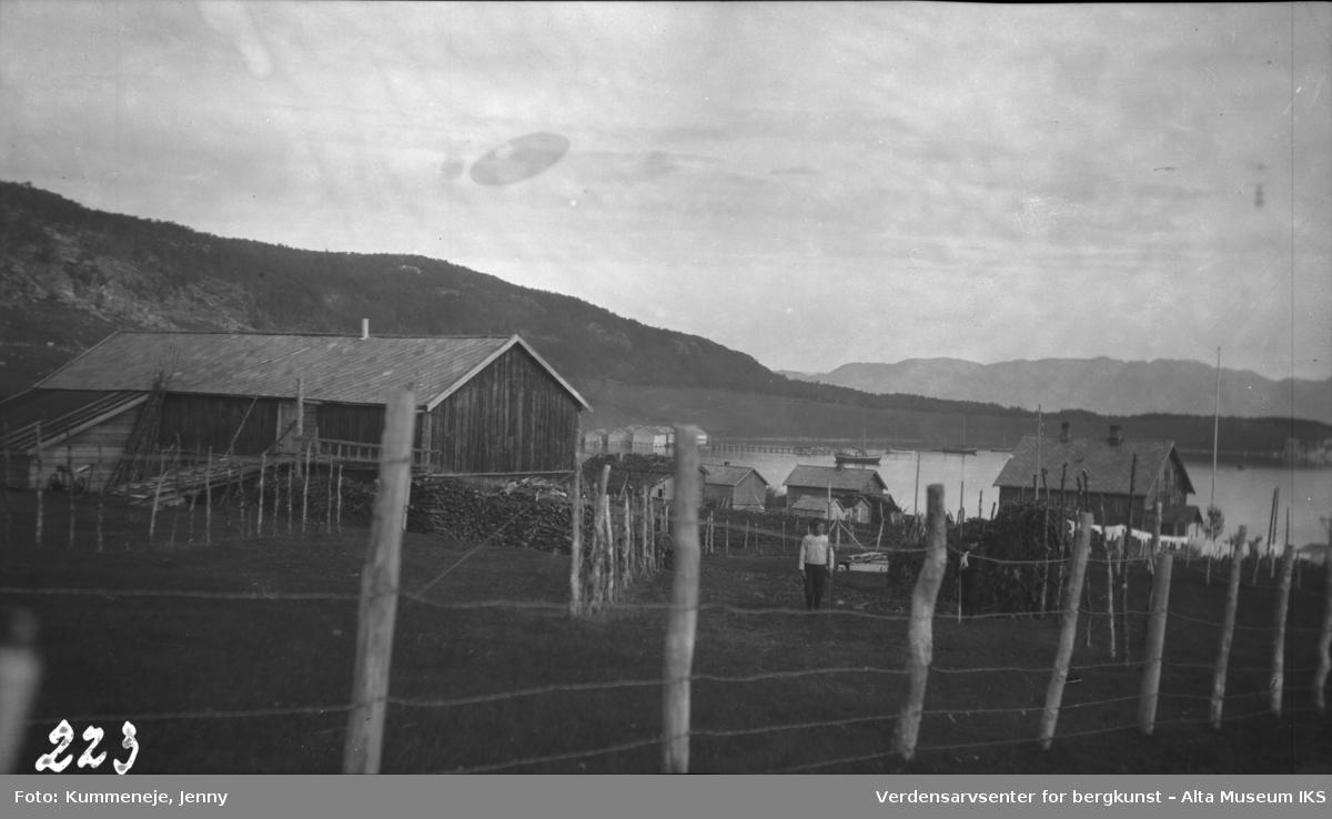 Inngjerdet gårdstun med bygninger og fjord i bakgrunn.1919