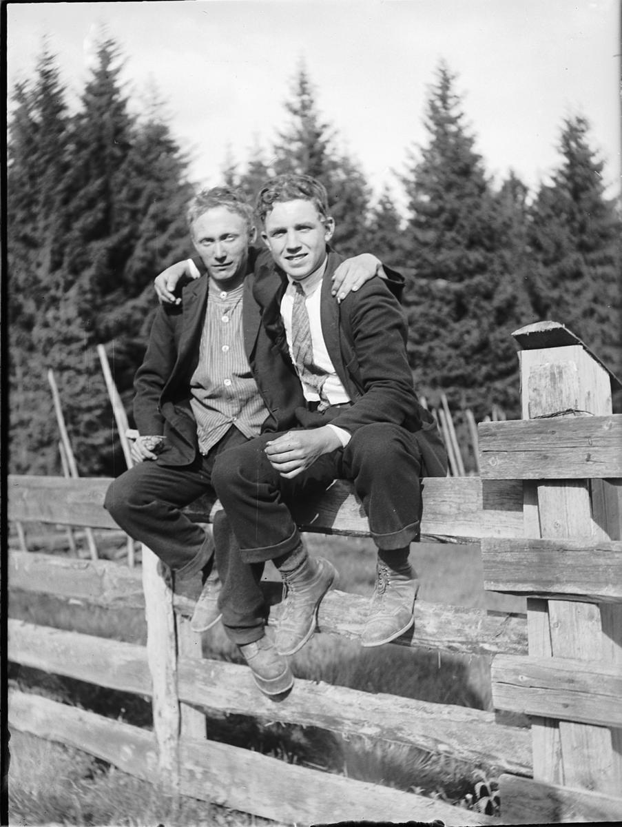 Eksteriør, skog. To ukjente menn sitter på et gjerde.