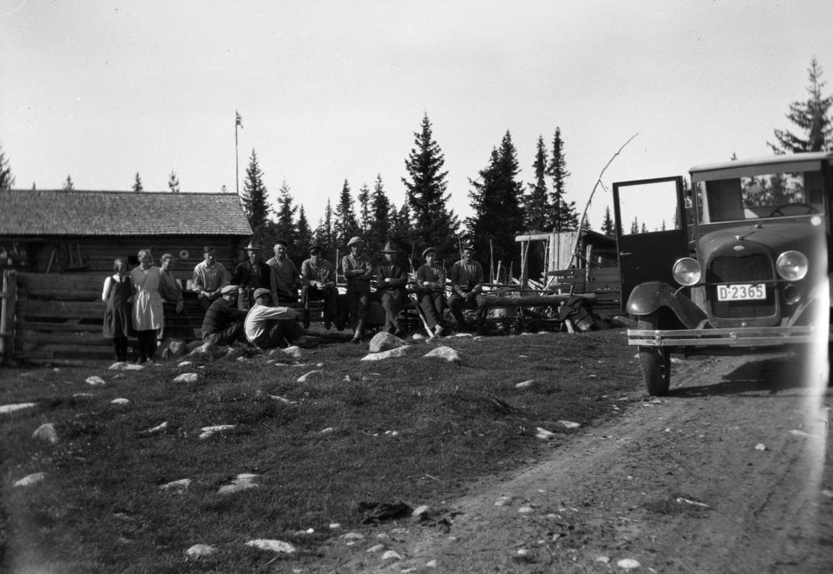 Gruppe 13 personer stående på en setervoll. Bil ned reistreringsnummer D-2365. Ford AA lastebil 1928-29.  Kan være Nysetra? På vegen fra Bjønnåsen og opp til Øyungen (Ringsakerfjellet)?