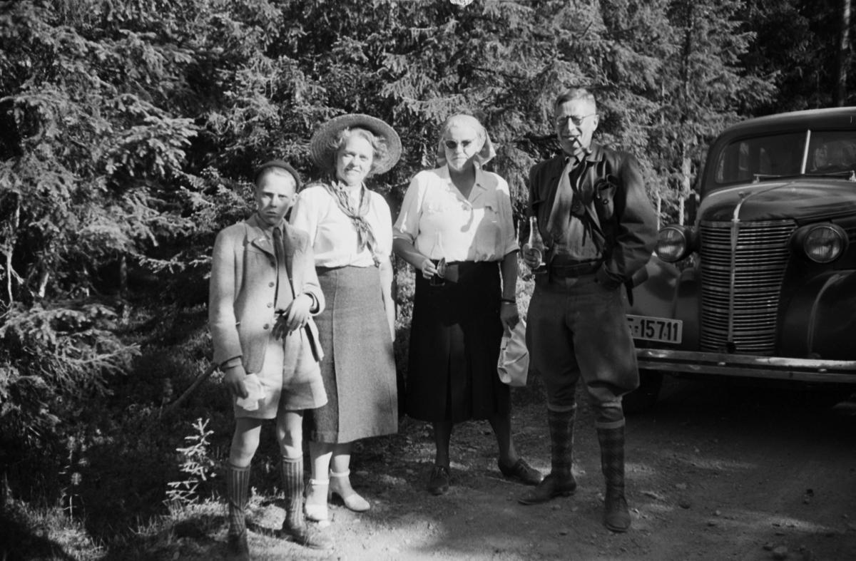 Buvika sagbruk, skogbefaring, Ringsaker allmenning. Juni 1949. To kvinner, en mann og en gutt foran en bil, Chevrolet 1938.