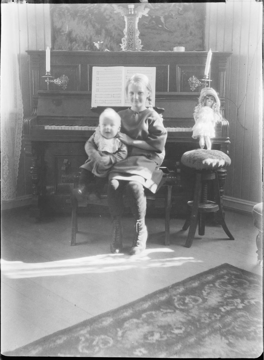 Interiør, stue. Jente med en baby på fanget sitter foran et piano og en dukke.