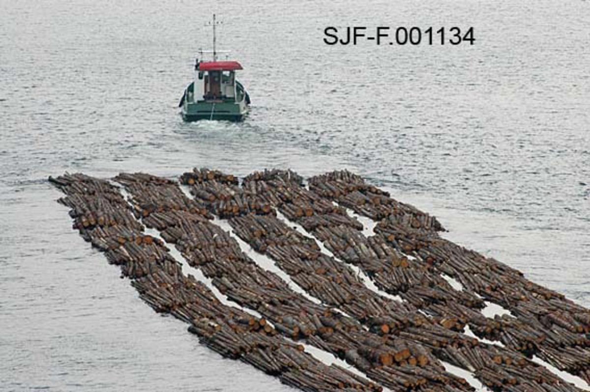 """Buntfløting av tømmer med slepebåt i Skiensvassdraget høsten 2005.  Fotografiet er tatt fra Nautesundbrua.  Det viser slepebåten Triset med et såkalt """"elveslep"""", som besto av fem rader med tjue tømmerbunter i hver, altså til sammen 100 bunter.  Under sjøfløting besto slepene av ti kjeder a førti bunter - altså til sammen 400 bunter, cirka 7 000 kubikkmeter tømmer.  Grunnen til at elveslepene gjennom Sauerelva var så mye mindre var at dette var et trangt og forholdsvis grunt farvann.  Fotografiet viser slepet og båten bakfra.   Slepebåten Triset ble bygd i Nederland i 1983.  Skiensvassdragets Fellesfløtningsforening kjøpte båten da den var ti år gammel, som en erstatning for slepebåten Einar Senior, som hadde vist seg dårlig egnet for drift i islagte farvann.  Fellesfløtningsforeningen kjøpte båten """"as is - where is"""" fra et konkursbo.  På dette tidspunktet var den registrert under navnet """"Geto"""".  Det var Fellesfløtningsforeningen som gav båten navnet Triset, etter en lokalitet ved innsjøen Bandak.  Båten hadde hatt et brannhavari i 1989, og det var etter dette at den fikk den kraftige 365 hestekrefters totakts dieselmotoren som Fellesfløtningsforeningen fikk så mye glede av."""