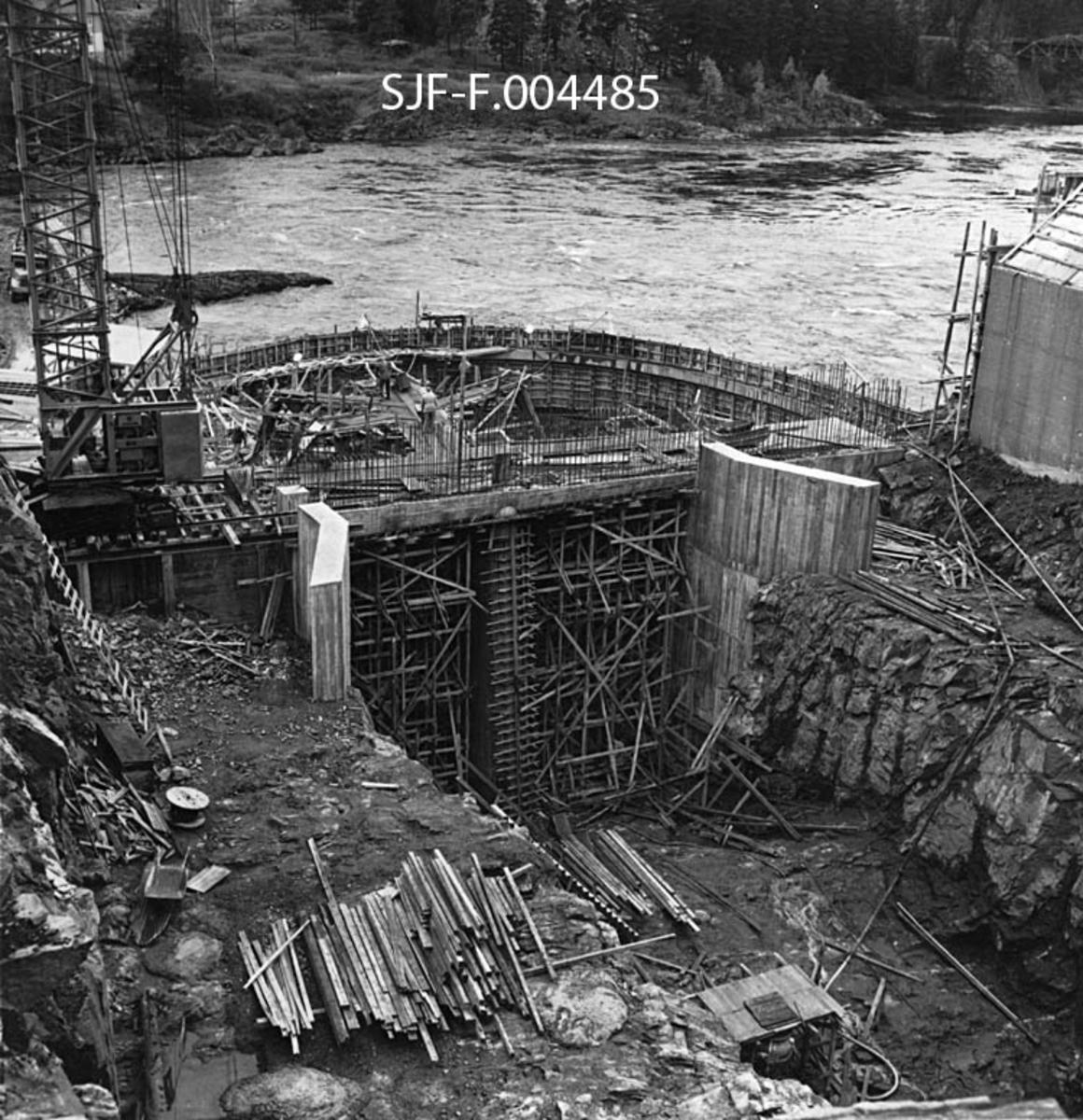 Tomta der Geithusfoss kraftverk skulle reises og der utløpet fra kraftstasjonen skulle plasseres.  Dette fotografiet, som er tatt i oktober 1960, viser anleggsområdet sett ovenfra, med det nedsprengte løpet for vannet som kom gjennom en tunnel fra et punkt ovenfor fossen til høyre i forgrunnen.  Fotografiet preges ellers av forskalinger for betongstøpearbeider, samt (lengre bak) av fangdammen, en bueformet skjerm av tre, som skulle hindre vann fra elveløpet fra å trenge inn på anleggsområdet.  Til venstre i bildet ser vi den nedre delen av ei diger anleggskran som ble brukt til å løfte materiell inn på og ut fra byggeplassen.  Bakenfor ser vi elveløpet, som nedenfor Geithusfossen gjør en sving før det passerer Kattfossbrua, som så vidt skimtes øverst i høyre hjørne på dette fotografiet.  Kraftverket ble satt i drift et snaut år etter at dette fotografiet ble tatt.