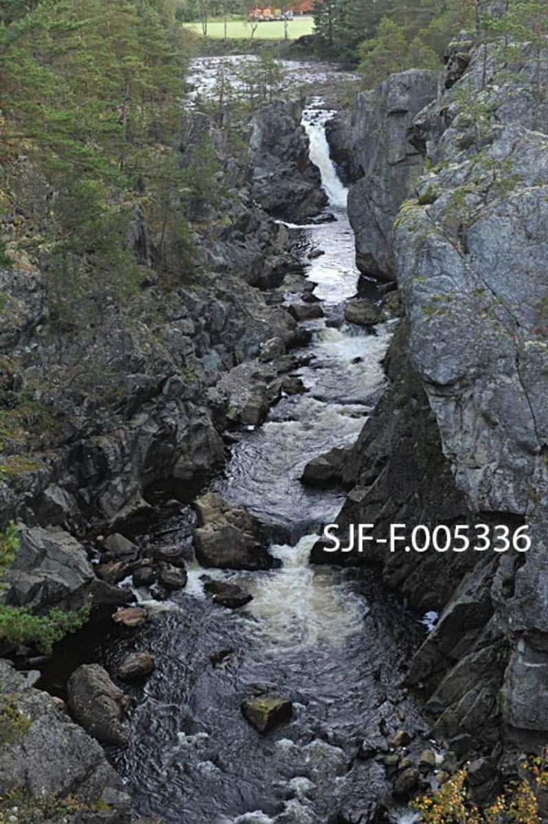 Satajuvet (i eldre tid også kalt «Satahullet») i Vallaråi i Seljord kommune i Telemark.  På strekningen mellom Flatsjå og Seljordsvatnet gjør dreier elva sørvestover¨i et fossefall ved garden Nordre Flatin, for deretter å dreie krapt sørøstover inn i et trangt juv like nedenfor.  Dette elvelandskapet skapte store problemer for fløtinga av tømmer fra Flatdal ned til Seljordsvatnet, og når fløtingsvirket satte seg fast i det djupe juvet, som var omgitt av steile bergflater, innebar det stor risiko å få det løst igjen.  Dette var en av årsakene til at myndighetene alt i 1858 tillot at det ble lagt ei spesiell avgift på 12 skilling per tylvt fløtingstømmerer her.  Midlene som kom inn fra denne avgiften skulle settes på en spesiell konto i Skiens sparebank.  Pengene som kom inn på denne måten skulle kommunestyret i Seljord disponere i henhold til en plan kanaldirektøren hadde fått utarbeidet for minering som skulle gjøre Vallaråi mer fløtbar.  Dette arbeidet pågikk i mange tiår, og sjøl om stadig flere hindringer ble sprengt vekk, hendte det at tømmeret satte seg fast her.  Dette fotografiet er fra den øvre delen av juvet, der det var et visst fall i elveløpet.  Nedenfor (til høyre for dette bildet) renner Vallaråi mer stille, men mellom to høye, bratte bergskrenter (jfr. SJF-F. 005331 - SJF-F. 005335)