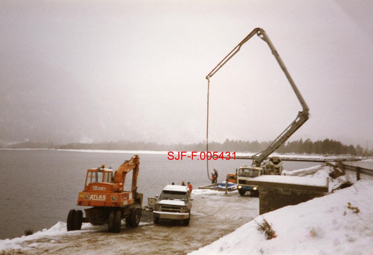 Fra bygginga av ny utislagsplass for tømmer ved Dalen, lengst vest i Bandakvatnet i Vest-Telemark.  Dette arbeidet ble utført i 1993, etter at utislagsarbeidet i mange år hadde skjedd fra en annen plass. Den opprinnelige utislagsplassen for lastebiltransportert tømmer ved Dalen ble etter hvert ble ansett for farlig, dels fordi det av og til kunne komme trillende stein fra den bratte lia ovenfor, dels fordi fyllinga som det ble tippet fra lot til å bli undervasket på et sted hvor terrenget under vannflata skrådde bratt ned til cirka 40 meters djup.  Fotografiet, som er tatt på en kald dag med snø på bakken og tåke i lufta, sto det en gravemaskin av merket Atlas, en robust stasjonsvogn (Chevrolet) og en lastebil med betongtrommel og treleddet hydraulisk kran med betongpumpe på den avsatsen som skulle bli tomt for målestasjon og velteplass.  Her arbeides det antakelig med fundamenter for «brakka» som skulle huse en ansatt fra Skiensvassdragets Fellesfløtningsforening og en fra Lågen-Telemark tømmermåling.  Ved denne brakka ble det også reist ei rampe for FMB-måling (fastmassebedømmelse) av tømmer.  Den nye utislagsplassen på Dalen kom også til å få ei såkalt «vogge», ei ramme for avlasting, bunting og hydraulisk tipping av tømmerlass på ei grund av stålbjelker ned mot et innlenset område i innsjøen nedenfor.  Dette skapte en langt tryggere situasjon for sjåfører og kjøretøyer enn tidligere, da lassene på Dalen ble tippet direkte fra bilene fra posisjoner ytterst på platået mot innsjøen.  Den betongstøpte konstruksjonen i vegskråningen til høyre i bildet var ei vaierbu, altså et lager for bind som ble brukt på tømmerlassene som skulle slås uti vassdraget fra Dalen.