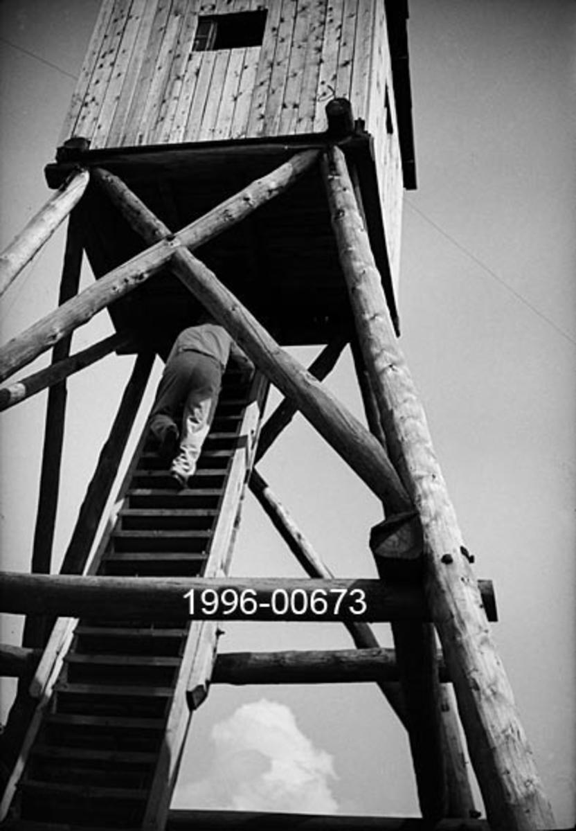 """Tårnet på Svartåsen skogbrannvaktstasjon i Lørenskog i Akershus.  Fotografiet viser den øvre delen av et brannvakttårn med stolper som bærekonstruksjon.  Stolpene er reist i en bratt, pyramidal form med ei noenlundkvadratisk utkikkshytte i bordkledd bindingsverk på toppen.  På bildet er en mann på veg opp stigen mot luka i golvet på utkikkshytta.   Svartåsen, hvor høyeste punkt er 361 meter over havet, er Lørenskogs høyeste punkt, og dermed også et bra utsiktspunkt. Det første brannvakttårnet på dette høydedraget ble reist for godseier Lorentz Meyer Boeck på Losby i 1901.  Dette tårnet skal ha vært 12 meter høyt.  Boeck var også viseformann i Akershus Amts Skogselskab, noe som naturligvis kan ha inspirert ham til å reise et brannvakttårn.  Skogbrannvern var nemlig en sentral sak for fylkesskogselskapene tidlig på 1900-tallet.  I 1932 ble det reist et nytt tårn på Svartåsen.  Dette tårnet var åtte meter høyt og hadde ei lita hytte på toppen. Det godseier Boeck som tok initiativet til å få reist det andre tårnet også, men i dette tilfellet fikk han refundert en vesentlig del av kostnadene fra Det norske gjensidige Skogbrand-forsikringsselskap, vanligvis kalt bare """"Skogbrand"""", som naturlig nok var meget opptatt av å stimulere brannforebyggende tiltak.  Det er sannsynligvis dette andre tårnet som er avbildet på dette fotografiet.  Vi vet foreløpig ikke hvor lenge dette tårnet var i drift, men da Skogbrand i 1960 henvendte seg til skogsjefen på Losby Bruk for å spørre om tårnet var tilfredsstillende utstyrt med peileappart for lokalisering av branntilløp, svarte forstmannen Nils Vøien at tårnet ikke eksisterte lenger.  """"Det hadde en såvidt ugunstig beliggenhet i forhold til det området det var ment å skulle dekke, at det ikke ble holdt vedlige og er nå revet"""", skrev skogsjefen.  Brevet fra Vøien forteller ikke eksakt når tårnet ble revet.  Han hadde vært skogsjef hos Katrine Boeck i 11 år da det nevnte brevet ble sendt.   Even Saugstadskriver følgende om brannvakttårnet """