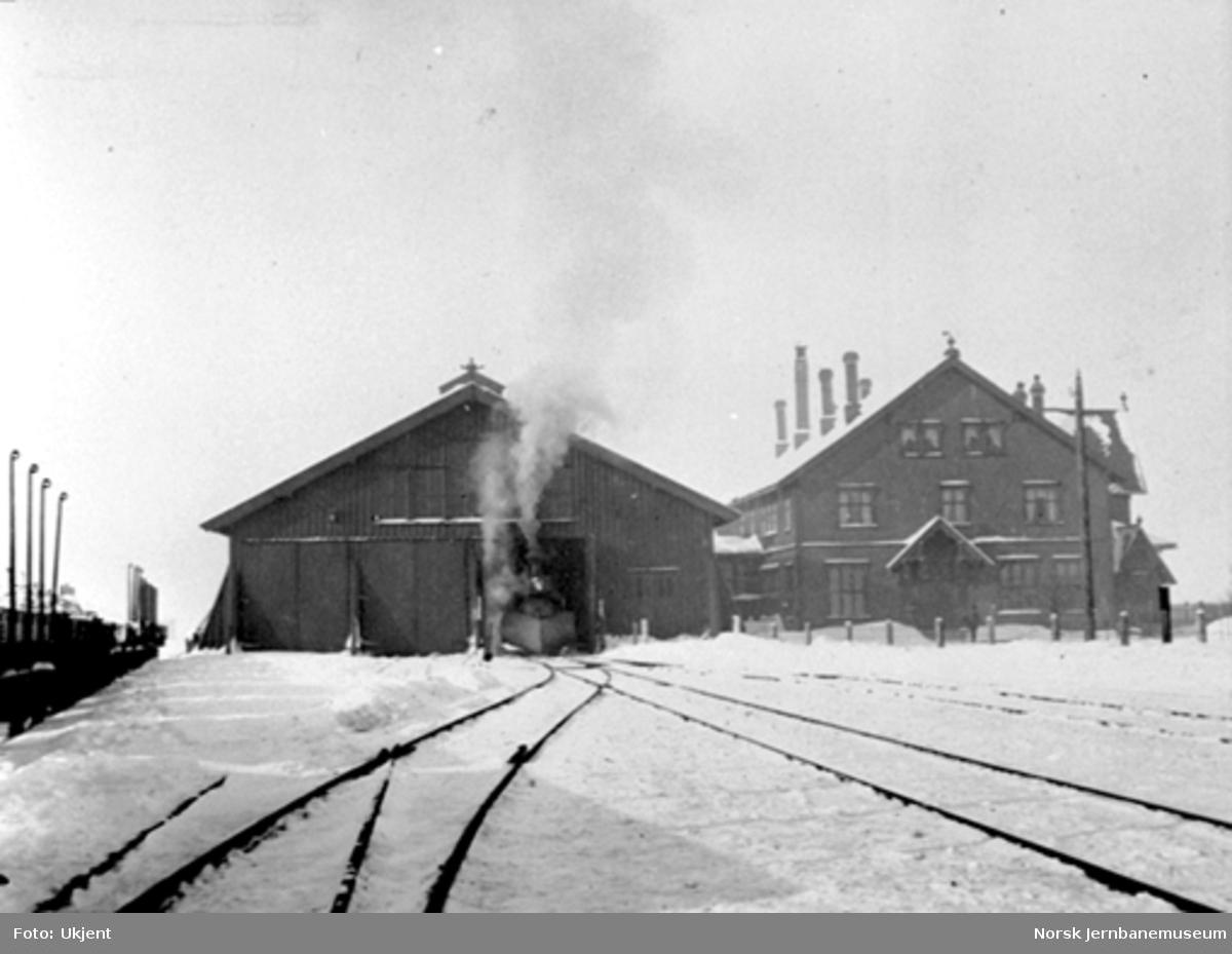 Vinterbilde fra Røros stasjon med forenden på et damplokomotiv utenfor toghallen
