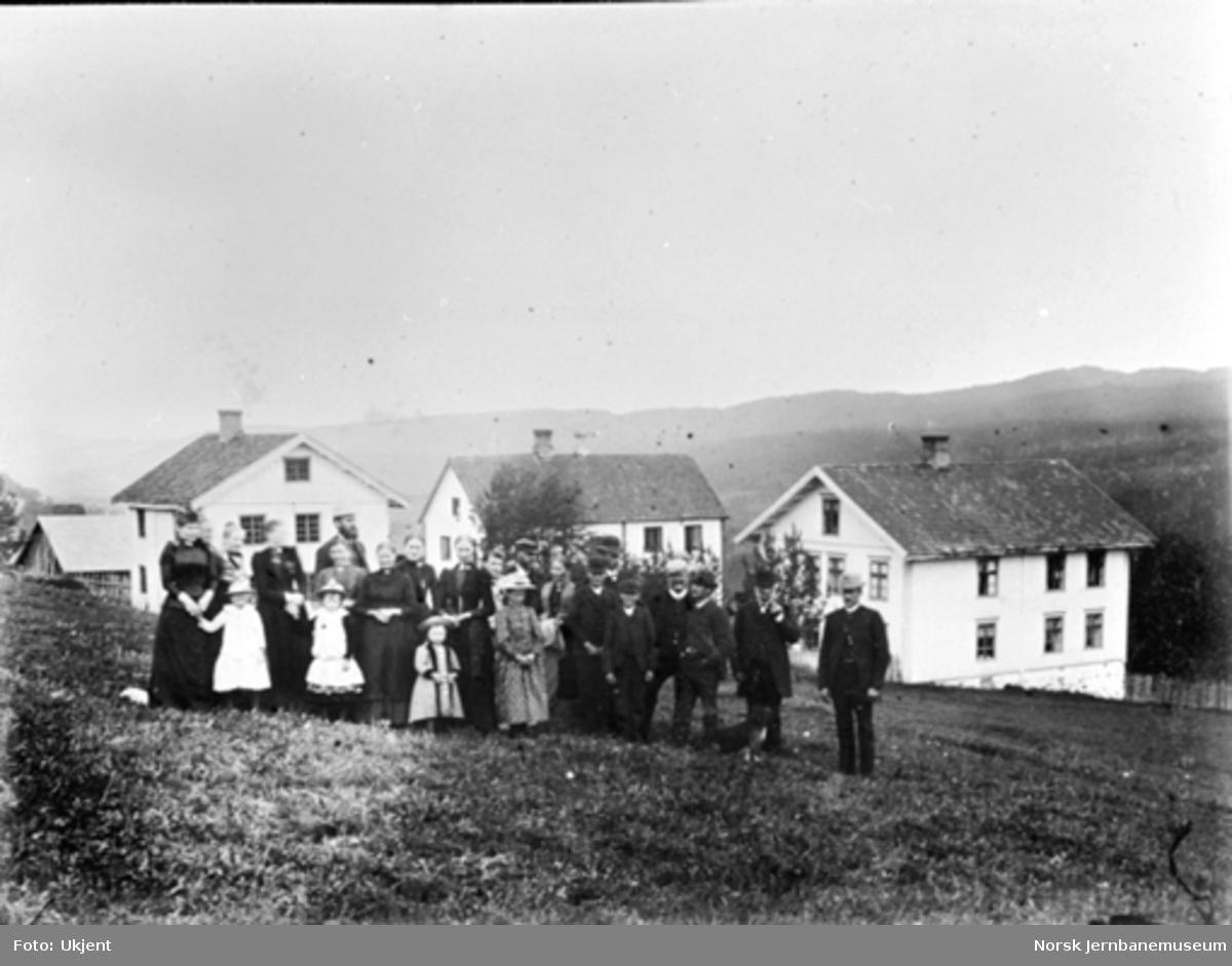 Gruppebilde med 23 personer på gården Stue i Biri; husene i bakgrunnen