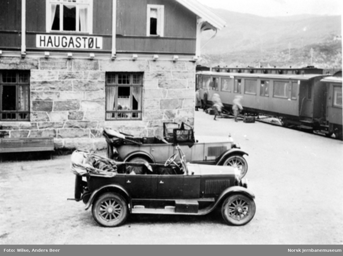 Haugastøl stasjon med to åpne personbiler i forgrunnen og tog på stasjonen