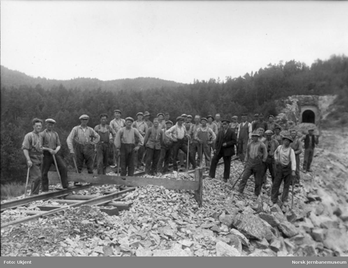 Gruppebilde av 33 anleggsarbeidere under justering av skinnegang på ny bane med tunnel i bakgrunnen
