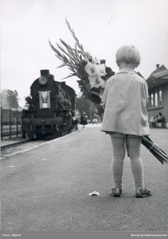 Barn med blomster hilser toget ved jernbanejubileet