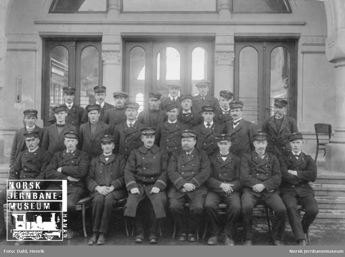 Gruppebilde av en del av stasjonspersonalet på Hamar stasjon foran stasjonsbygningen