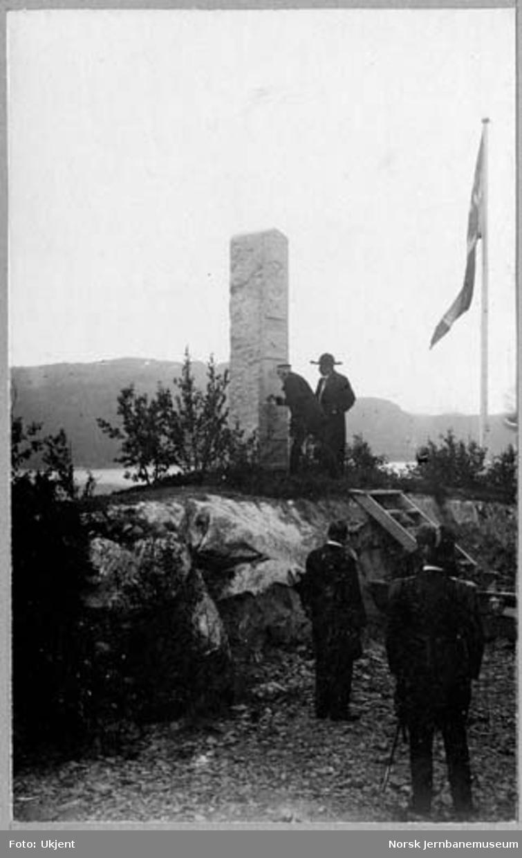 Ofotbanens og Malmbanans høytidelige åpning : kongen skriver sitt navn på bautasteinen ved banens nordligste punkt