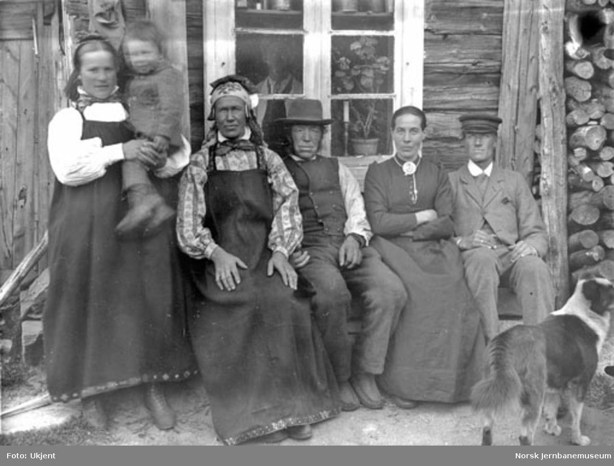 Gruppebilde av seks personer utenfor et gårdsbruk, trolig Nygård vest for Haugastøl