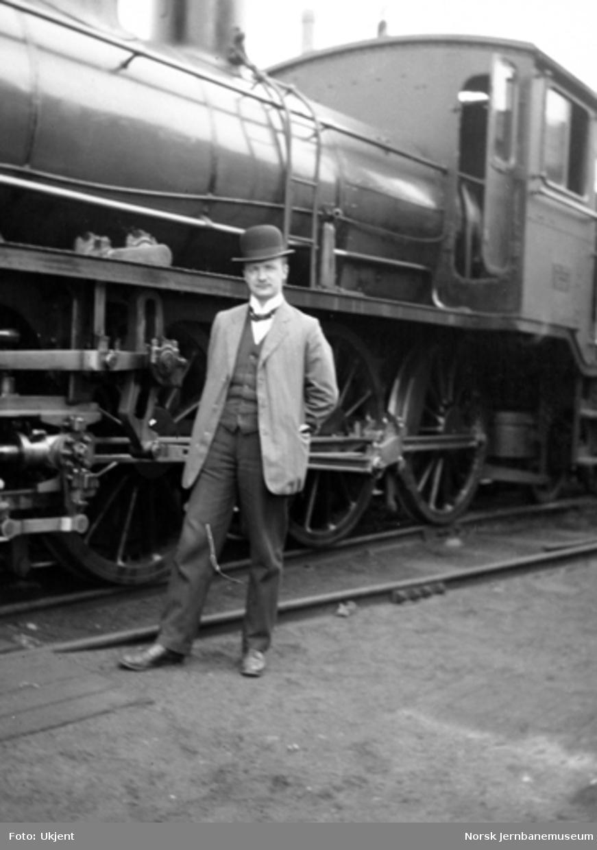 Ukjent mann foran et damplokomotiv av type 18
