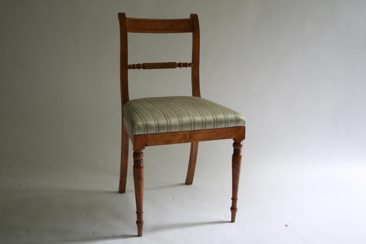 """En av seks stoler.  Fremben er dreid og dekorformet. Polstret sete med trekk trolig i ulldamask. Striper i grønt, lysegrønt og hvitt. Smal stripe av mørkere tre innlagt på ryggbrett. Spile under  ryggbrett har snodd (""""tau-"""") dekor."""