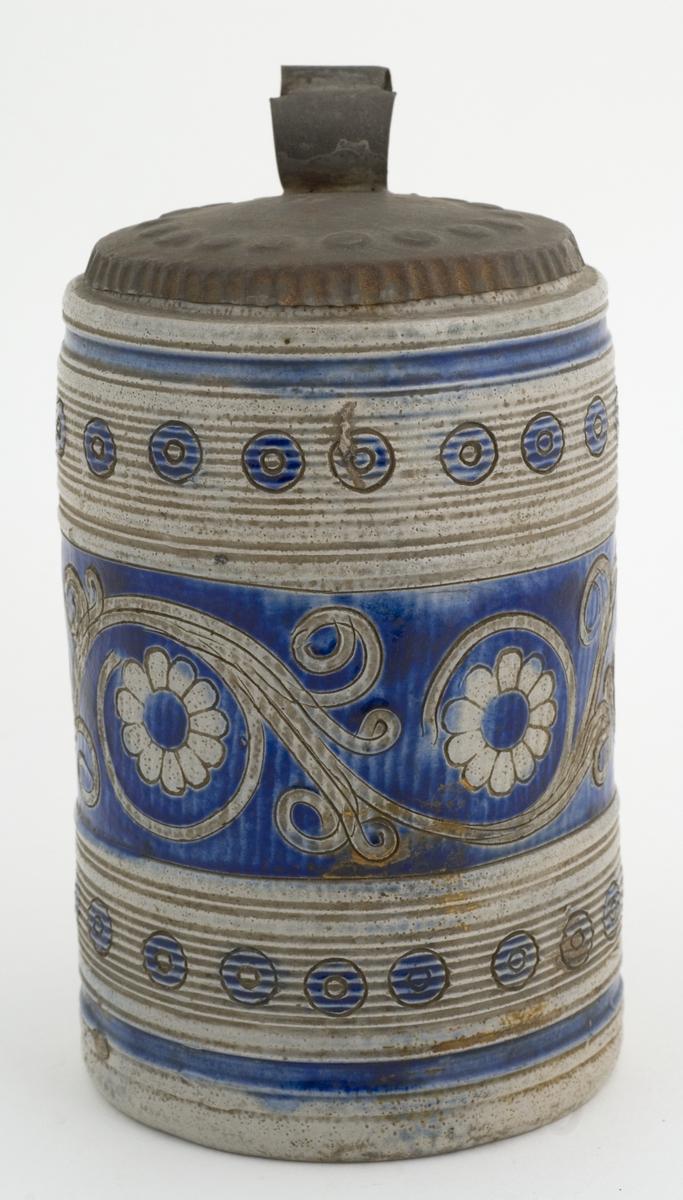 """Krus i grå keramikk av en type som stammer fra Westerwald-området i Tyskland. Karakteristisk er risset og stemplet dekor og pålagte relieffer, farget med koboltblått og senere også manganfiolett, under klar saltglasur. Dette lave, sylinderformete kruset kalles """"Humpen"""" og ble masseprodusert gjennom hele 1600 og 1700-tallet.  Kioplett lokk."""