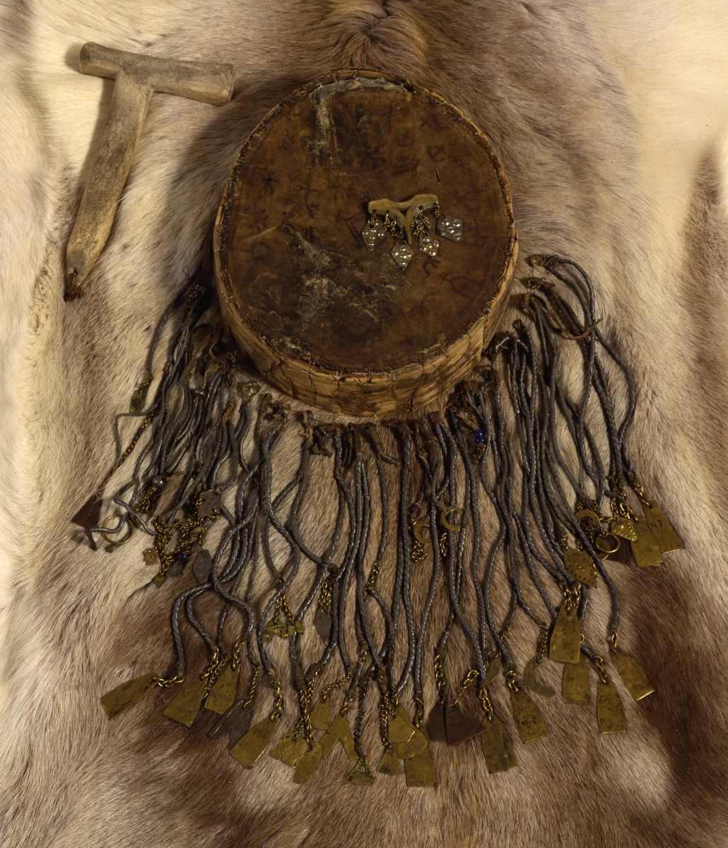 Oval tromme med håndtak på undersiden. Skinnet har malte symboler.