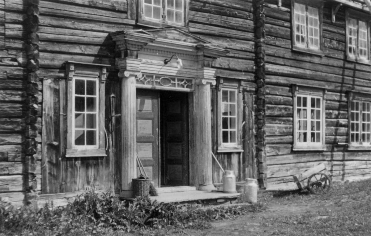 Inngangspartiet med portal på Frøset gård i Soknedal i Sør-Trøndelag. Melkespann og kjerre ved trammen på tømmerbygning.